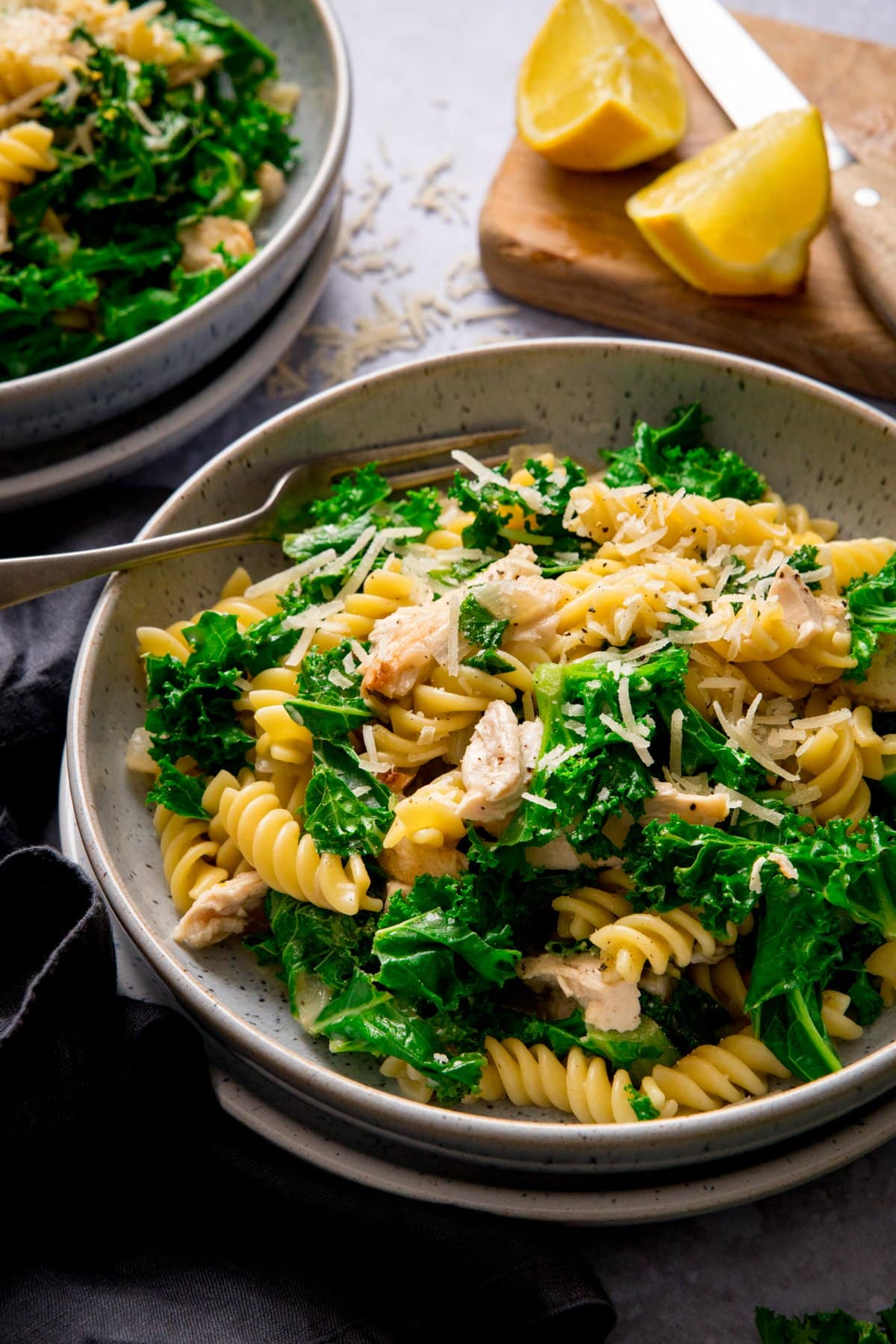 Bowl of garlic chicken pasta and kale with a fork in. Wedges of lime and further bowl of pasta at the top of the shot