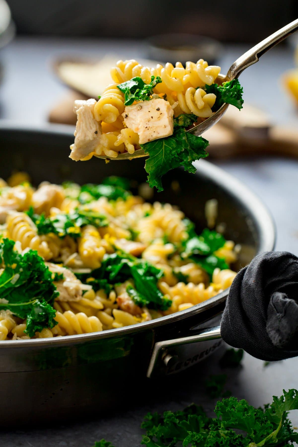 Spoonful being taken from a pan of chicken, kale and pasta