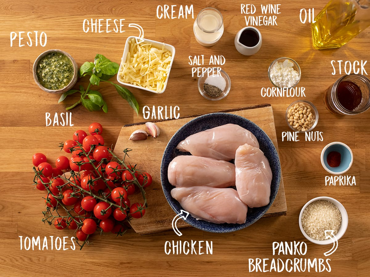 Ingredients for baked pesto chicken on a wooden table