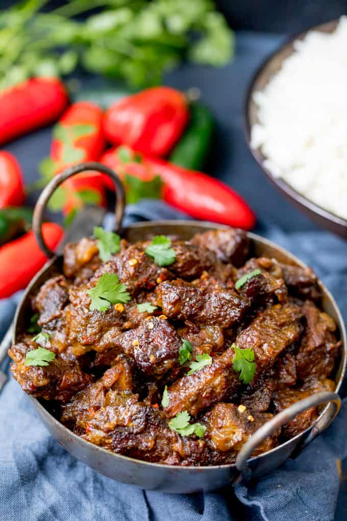 Beef Rendang in a metal bowl with rice and chillis in the background