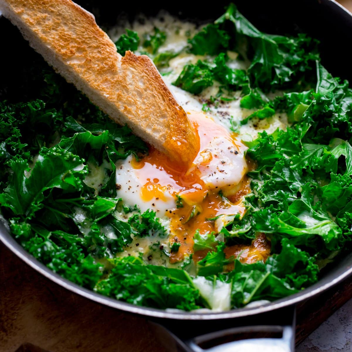 A toast soldier being dipped into a runny egg yolk in a pan of egg and cheesy kale