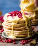Lemon sauce being poured onto stack of pancakes
