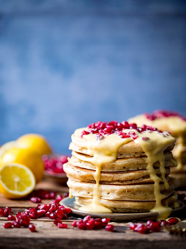Stack of ricotta pancakes topped with lemon sauce and pomegranate with a blue backdrop