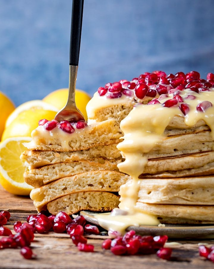 Slice being taken out of a stack of ricotta pancakes with lemon sauce