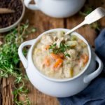 Chicken pot pie soup in a white bowl with fresh thyme on top.