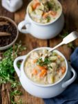 Chicken pot pie soup in a white bowl with thyme on top.