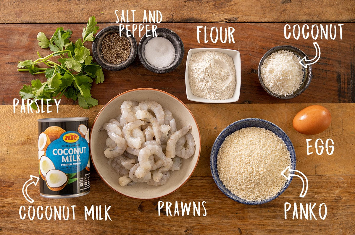 Ingredients for coconut shrimp on a wooden table
