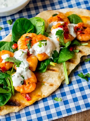 Garlic chilli prawns with spinach and yogurt dip on homemade flatbread on a piece of blue chequered paper