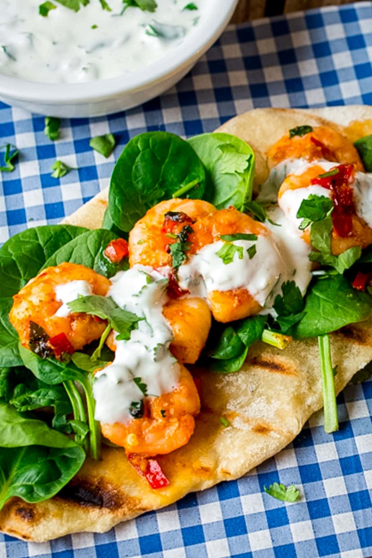 Tall image of Garlic chilli prawns with spinach and yogurt dip on homemade flatbread on a piece of blue chequered paper