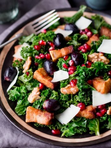 Comforting warm kale salad with crisp slow-cooked pork belly & pomegranate dressing