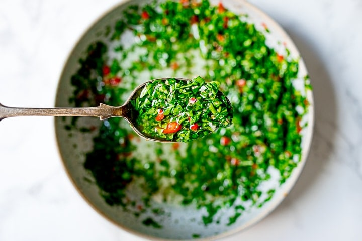 Spoonful of spicy chimichurri above a bowl