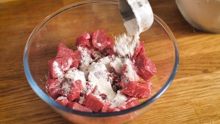 Coating cubes of beef in flour for a steak pie
