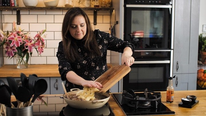 Nicky Corbishley adding potatoes into a pan for a meat and potato pie