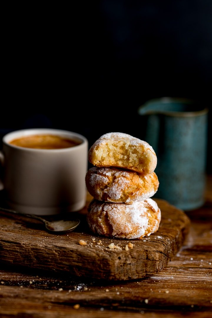 Tall image of amaretti cookies on a wooden board against a dark background. Coffee and milk jug in background.
