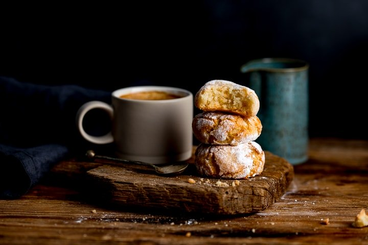 Amaretti cookies on a wooden board against a dark background. Coffee and milk jug in background.