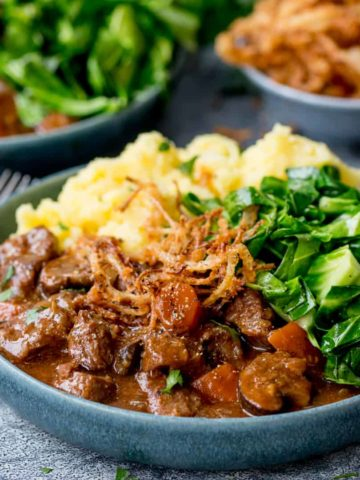 Square image of a bowl of beef and Guinness Stew with mashed potatoes and green cabbage