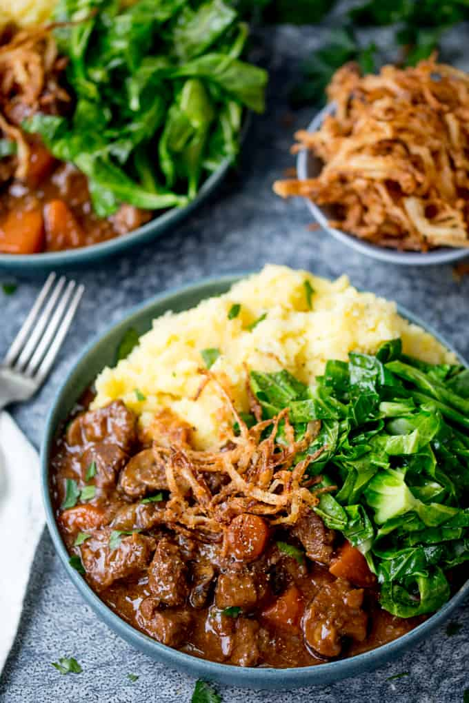 Bowl of beef and Guinness stew with mashed potato, greens and crispy onions.