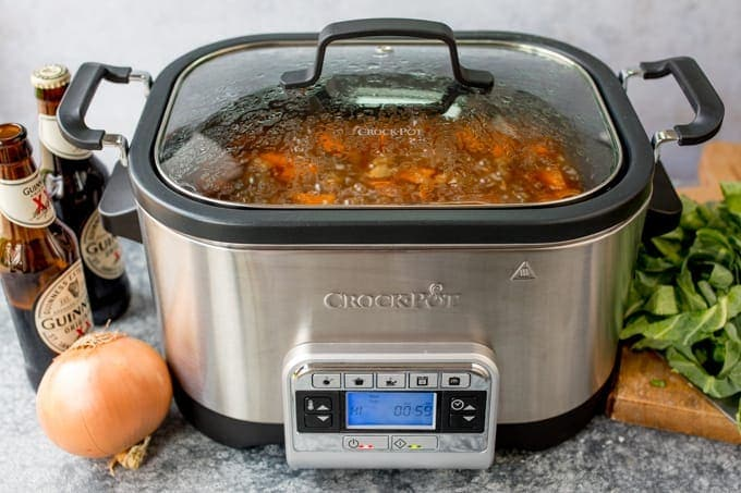Crockpot with beef stew. Onions, Guinness and cabbage on the table.