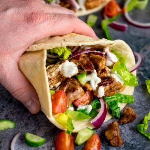 Chicken Shawarma in a pita being held by a hand