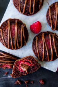 Tall image of mini chocolate cakes with fresh raspberry and Nutella centre, drizzled with Nutella.