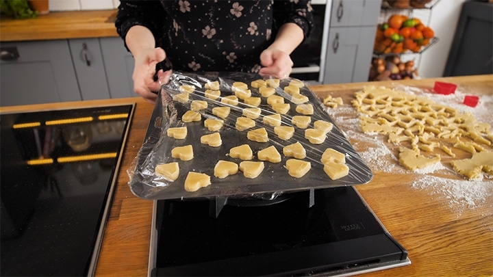 Shortbread heats on a tray, covered in clingfilm