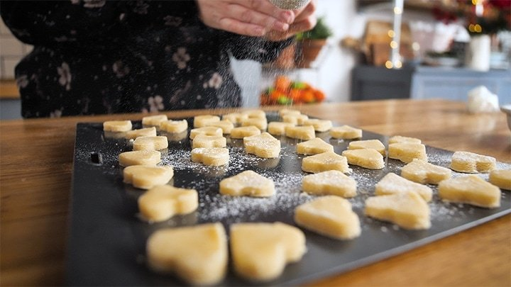 uncooked shortbread hearts on a tray with icing sugar being sprinkled on