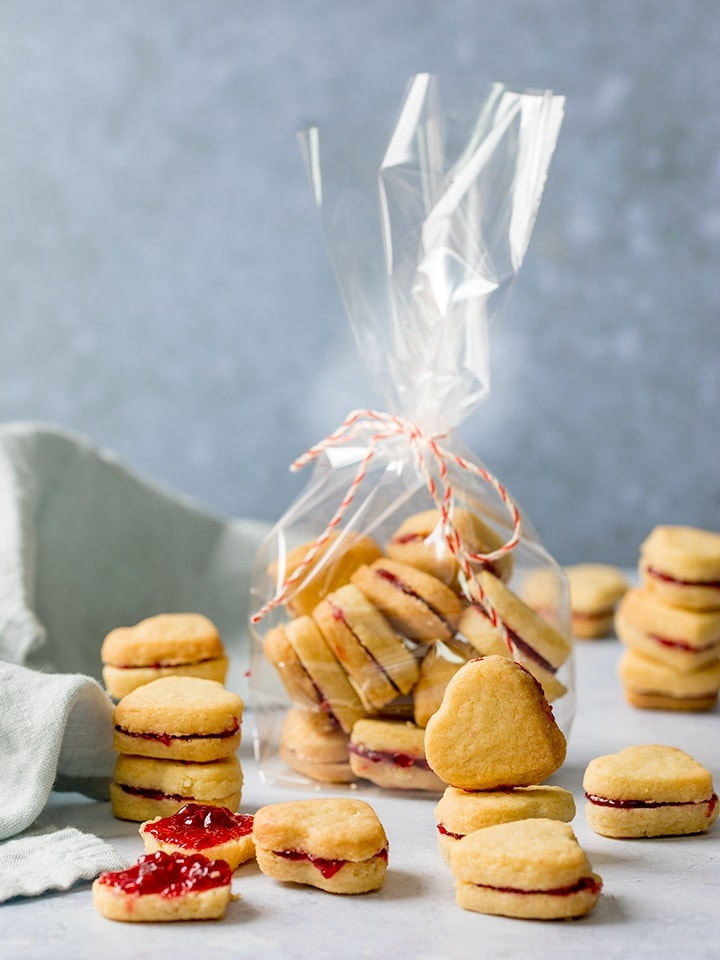 Stack of jam-filled, heart-shaped valentine shortbread cookies, plus some in a gift bag on a light blue background