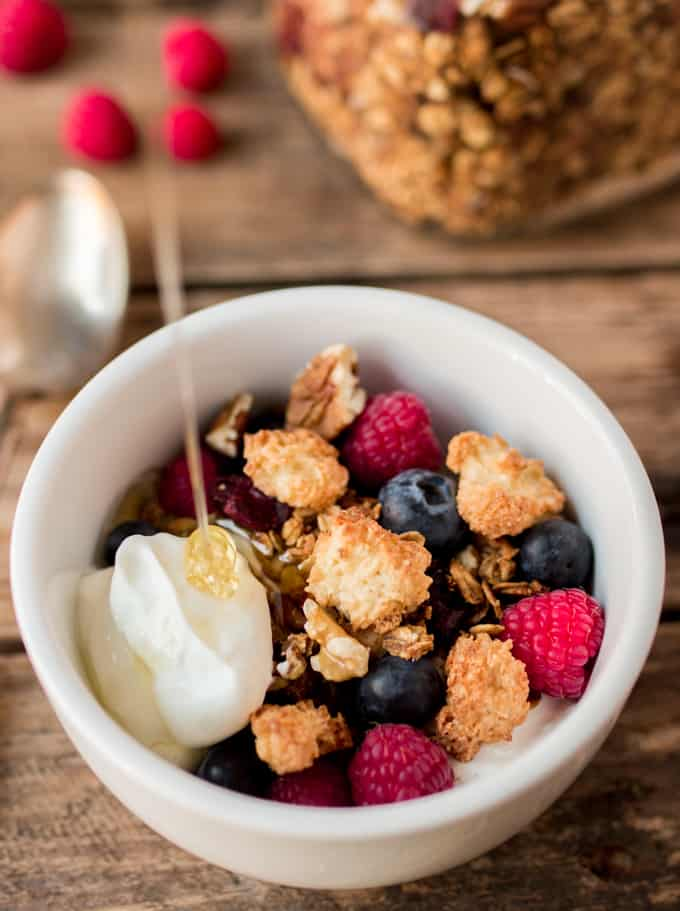Bowl of Coconut Macaroon Granola with Greek yogurt and honey being poured onto