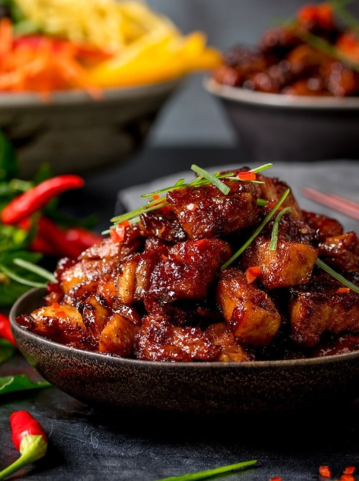 Close up image of bowl of Chinese sticky pork belly pieces.