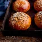 square image of seeded brioche buns on a tray