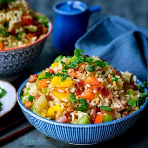 Square image of a bowl of fried rice on blue background