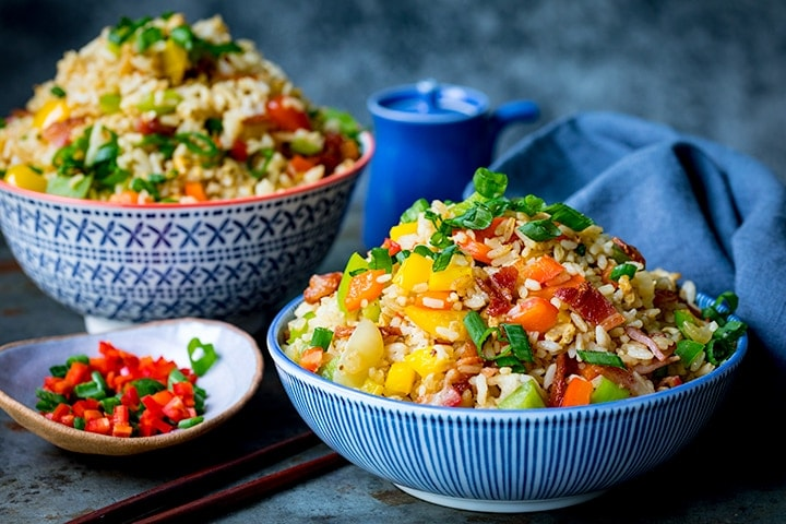 Two bowls of fried rice and a small dish of chopped chillies