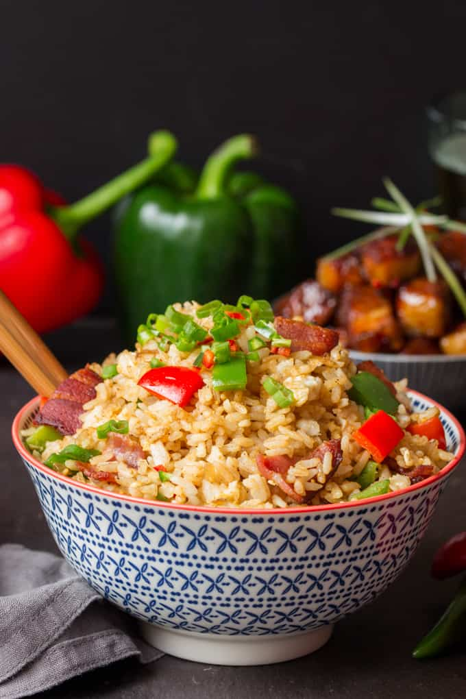 Fried Rice in a bowl with peppers and belly pork in the background