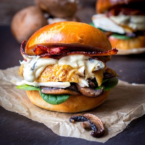 Chicken, bacon, spinach and creamy mushrooms on a brioche bun on a piece of parchment