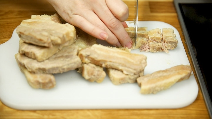 Pieces of cooked pork belly being sliced on a chopping board.