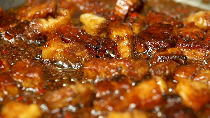 Pieces of pork belly in bubbling chinese style sauce in a pan.
