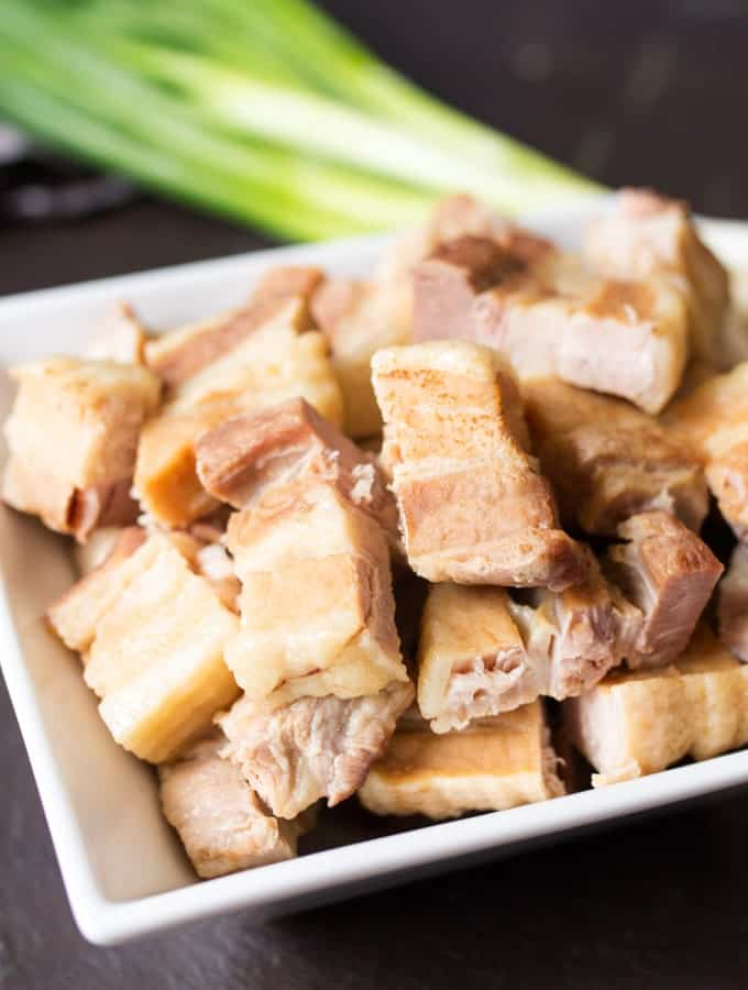 Close up picture of pieces of Belly Pork after it has been boiled with spring onions out of focus