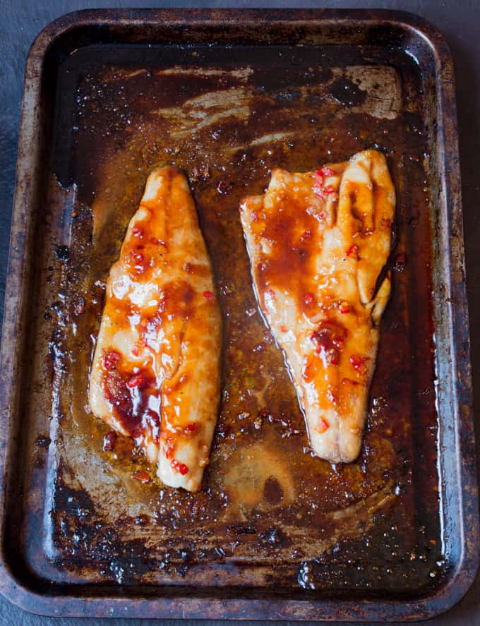2 cooked sea bass fillets on a tray with sticky asian sauce on top.