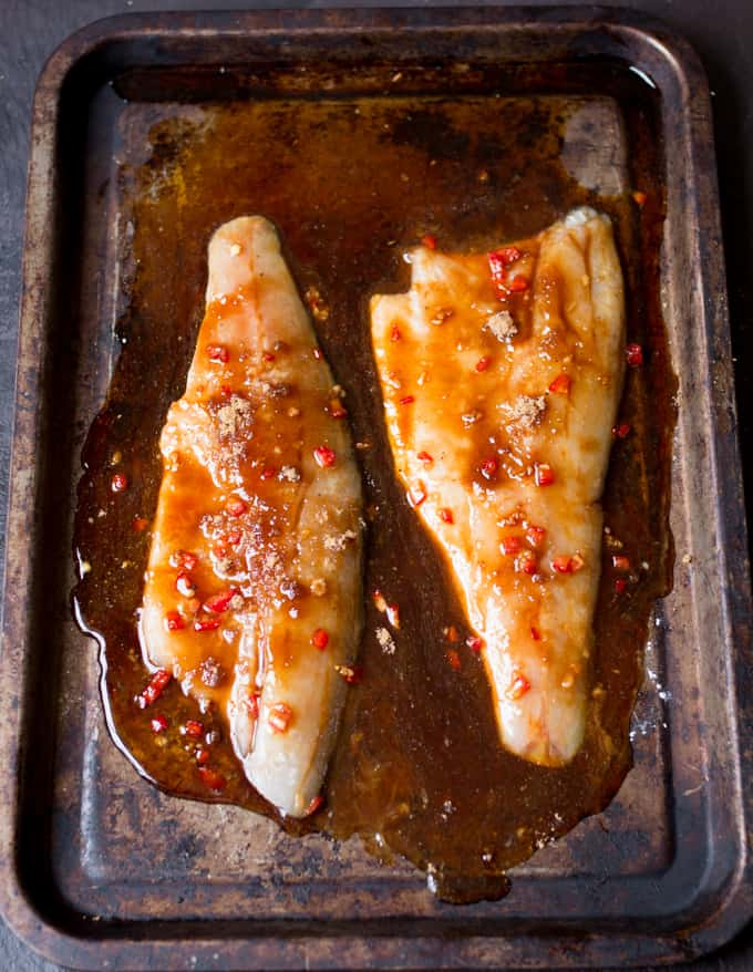 2 sea bass fillets on a baking tray with asian sauce on top.