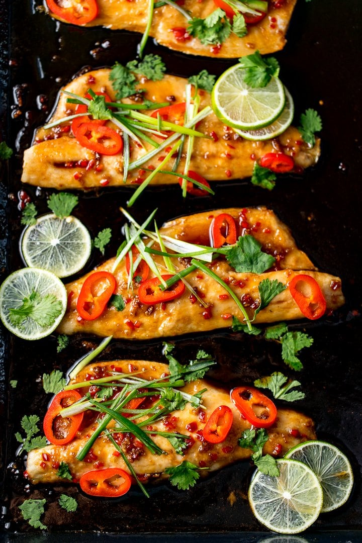 Sticky Asian-style baked seabass fillets on a tray with chillies, spring onion and lime
