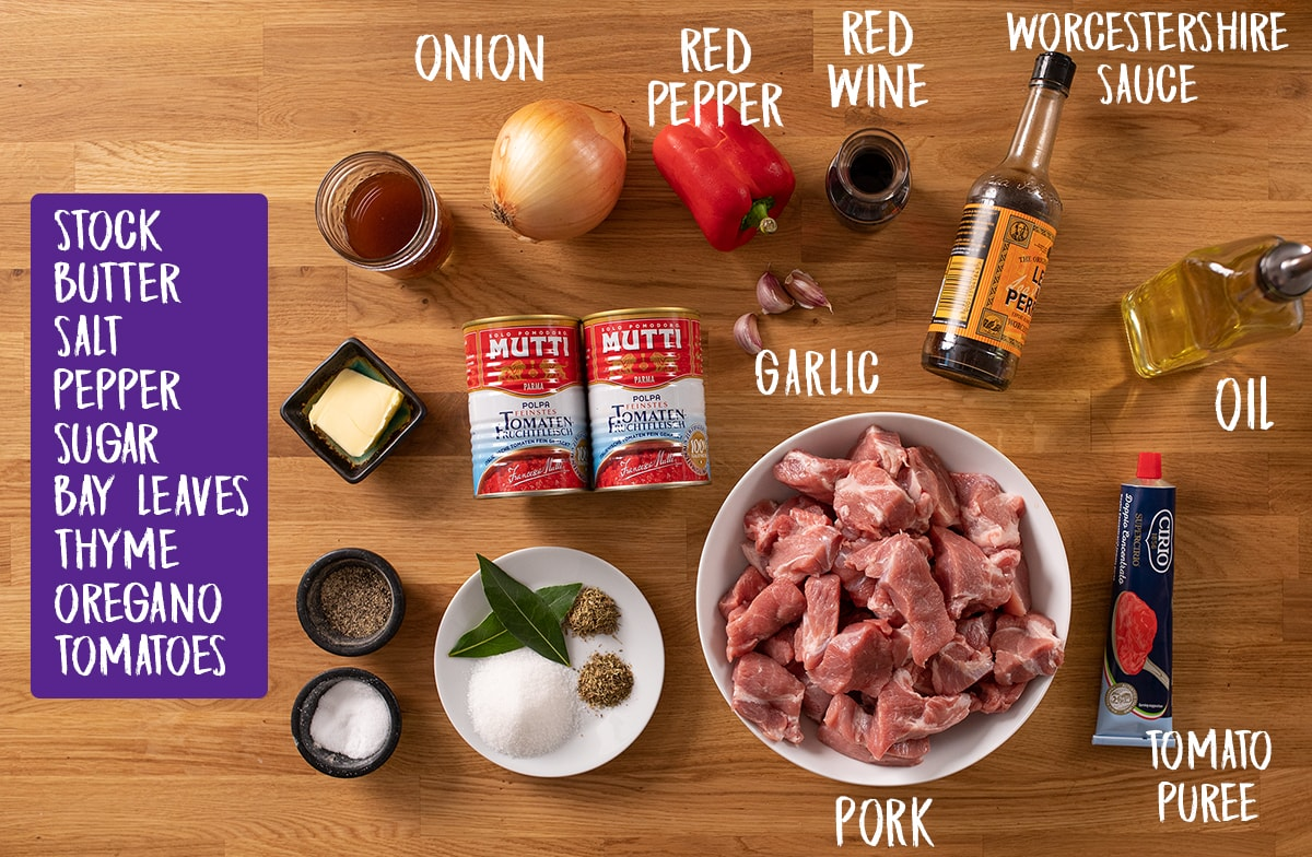 Ingredients for slow cooked pork ragu on a wooden table