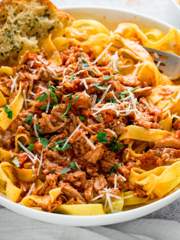 slow cooked pork ragu in a white bowl with pasta and garlic bread