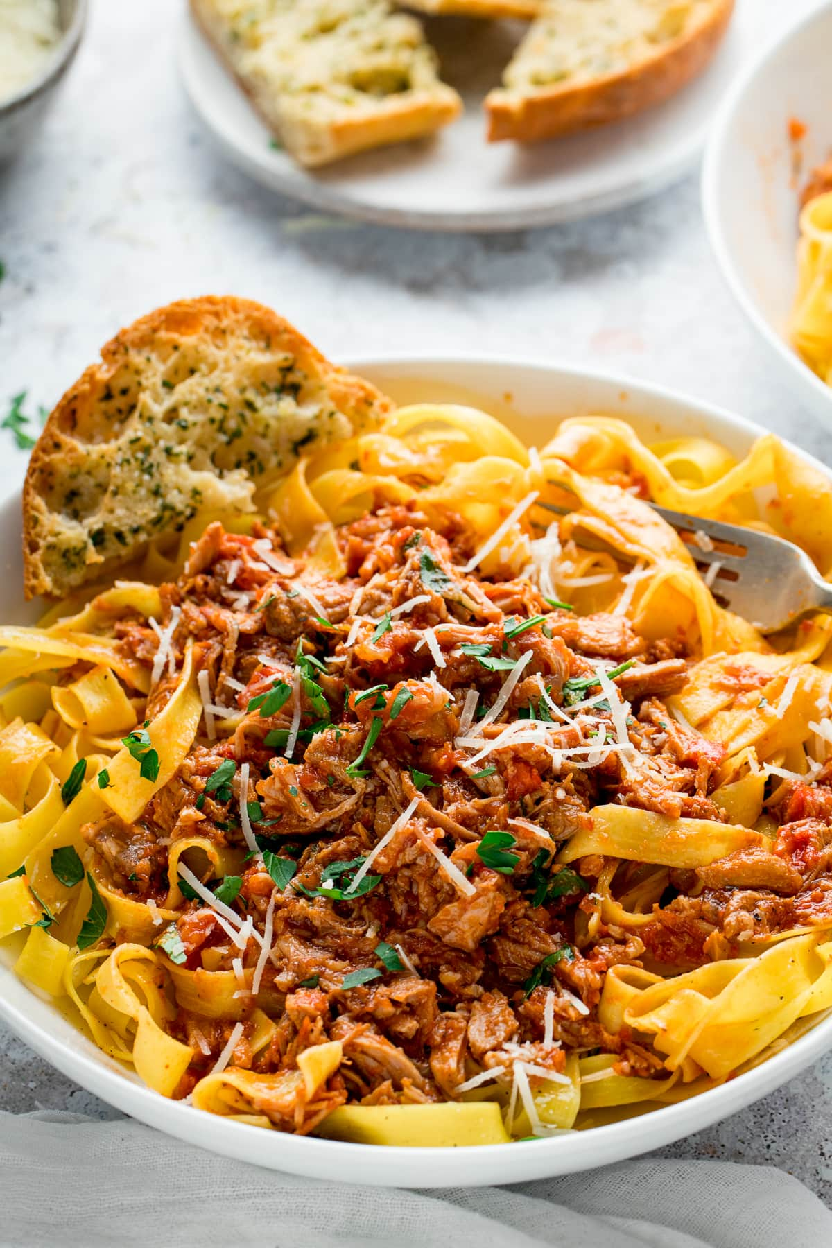 slow cooked pork ragu on top of tagliatelle in a white bowl with garlic bread