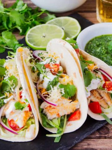 Fish Tacos with a mountain of toppings and TWO sauces - A garlic Mexican crema and a hot green chilli salsa!