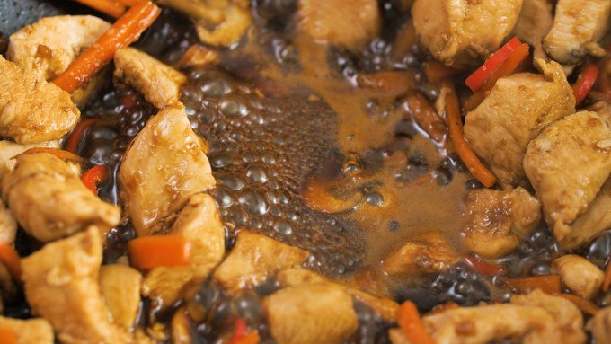 Chicken with Asian-style sauce bubbling in a wok