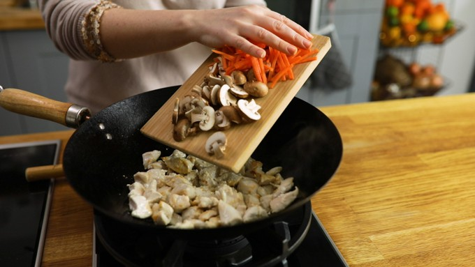 Adding mushrooms and carrot to a wok with Chicken pieces