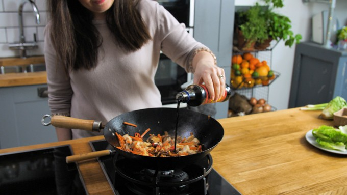Pouring soy sauce into a wok will Asian chicken and vegetables