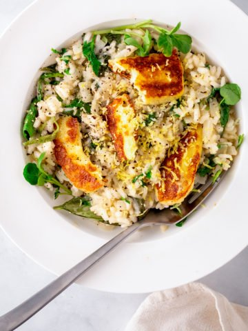 Overhead Picture of lemon risotto topped with fried haloumi slices in a white bowl.