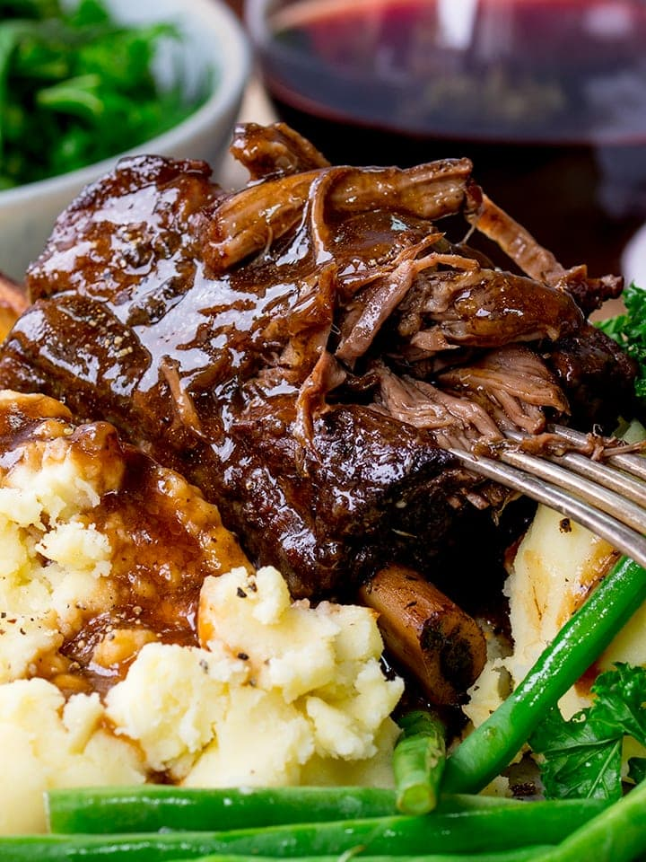 Close up of Slow cooker short ribs with gravy being pulled apart