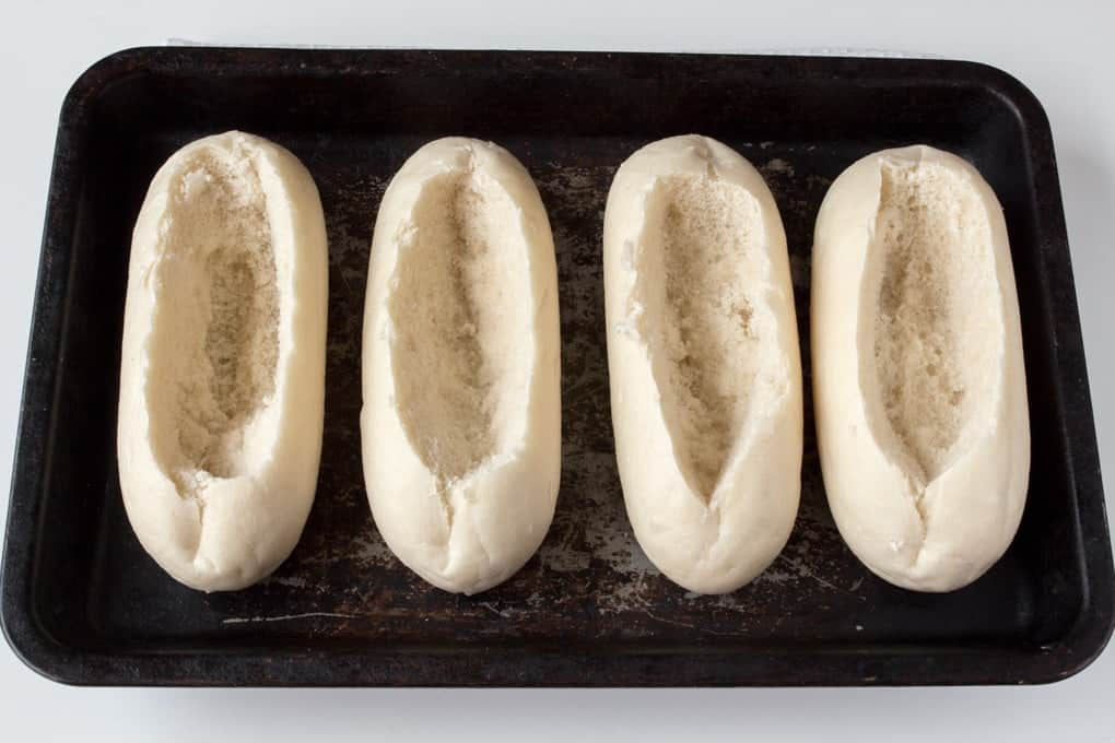 4 bread rolls on a tray with the insides scooped out